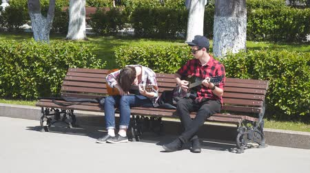 com cordas : SAMARA, RUSSIA - JUNE 21, 2018: Two young street musicians with guitars on a Park bench