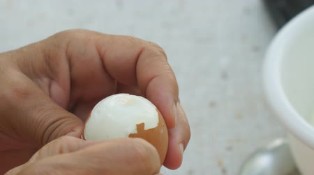 cálcio : A woman cleans a boiled chicken egg from the shell
