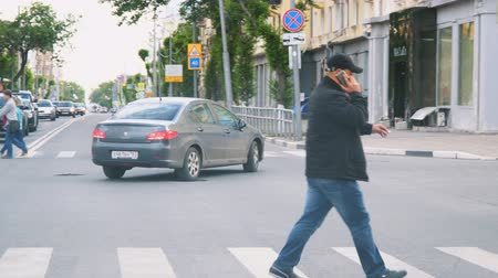 crossover : SAMARA, RUSSIA - JUNE 31, 2018: A man crossing the road and talking on the phone Stock Footage