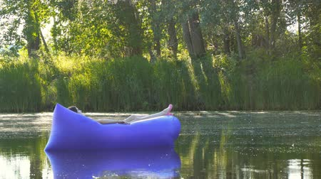 curtimento : A young woman lying on an airbed takes sunbathing and sails along the river. Purple inflatable mattress Stock Footage