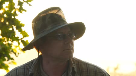 hnědožlutý : Portrait of a man in dark glasses and khaki protective hat. A man looks away and then leaves Dostupné videozáznamy