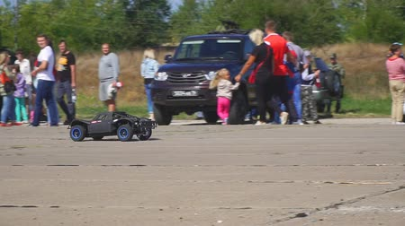 přihrádka : Samara, Russia - September 11, 2018: A black radio-controlled model of a car drives fast in the park. Slow motion Dostupné videozáznamy