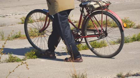 macskaköves : Elderly man walking down the street with an old Bicycle