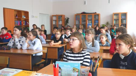 klasa : CHAPAEVSK, SAMARA REGION, RUSSIA - OCTOBER 24, 2018: School kids in the classroom sitting at their desks and listen to the teacher