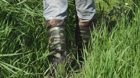 caqui : A man walks along the thick grass in khaki boots of protective color