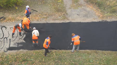 fixing : CHAPAEVSK, SAMARA REGION, RUSSIA - OCTOBER 17, 2018: Road street repairing works. Construction workers during asphalting road. Manual labor in construction Stock Footage