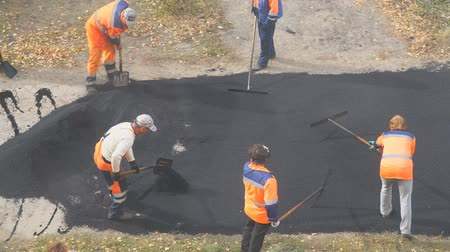 çakıl : CHAPAEVSK, SAMARA REGION, RUSSIA - OCTOBER 17, 2018: Road street repairing works. Construction workers during asphalting road. Manual labor in construction Stok Video