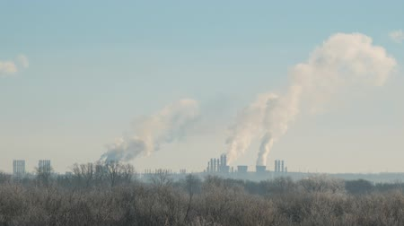 poluir : Environmental pollution. Modern landscape with factory pipes at a distance from which smoke is polluting the air. Camera panning Stock Footage