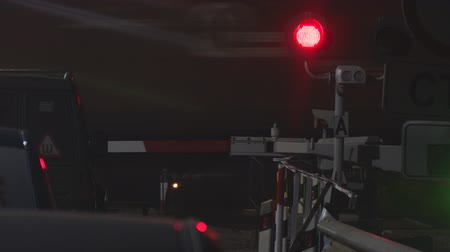 approaching subway : Flashing red traffic light at a railway crossing at night on the background of a passing train