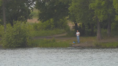 шнур : Fisherman on the opposite shore of the lake with a fishing rod. Long shot