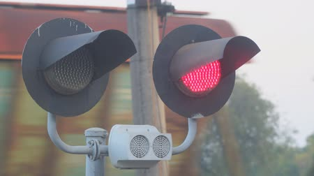 approaching subway : Flashing red light at the railway crossing on the background of a passing train Stock Footage