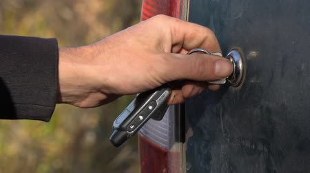 dobrado : A man closes or opens the trunk of the car with a key