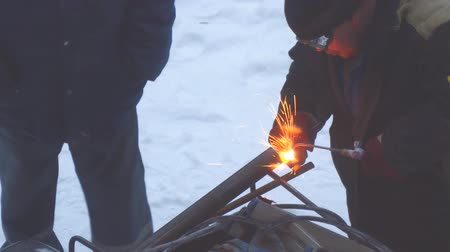 ironworks : Welder welds metal parts using gas welding outdoors in winter