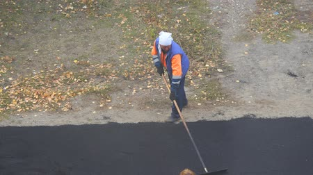 paving : Road street repairing works. Female worker during asphalting road. Heavy female manual labor in construction Stock Footage