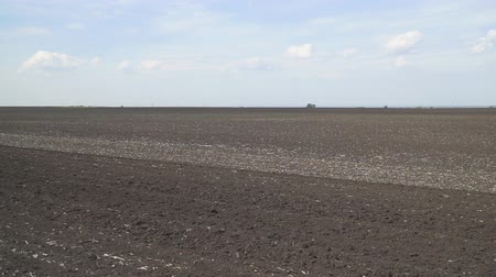furrow : Plowed earth under a cloudy sky. Arable land and sky. Camera panning