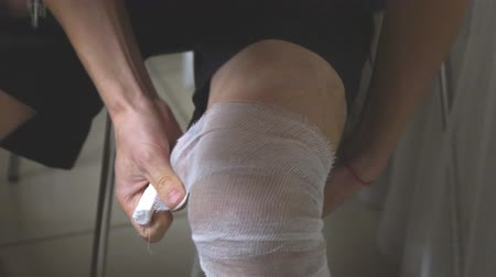 rana : A man puts a bandage on his leg. Bandages the leg