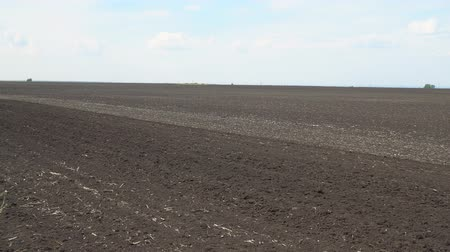 tillage : Plowed earth under a cloudy sky. Arable land and sky. Camera panning