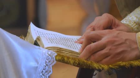 cassock : The book is in the hands of a priest or clergyman
