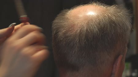 бритье : Woman hairdresser cuts a man with a receding hairline with scissors. Selective focus Стоковые видеозаписи