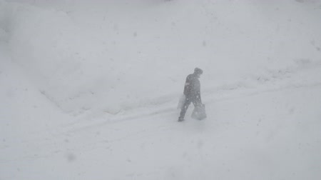 sıkışmış : A man goes into a snowstorm on the road with bags in his hands Stok Video