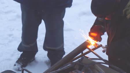 laboring : Welder welds metal parts using gas welding outdoors in winter