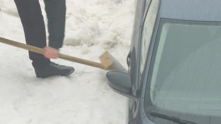 kazılmış : A man digs a shovel of snow from a car stuck in the snow Stok Video