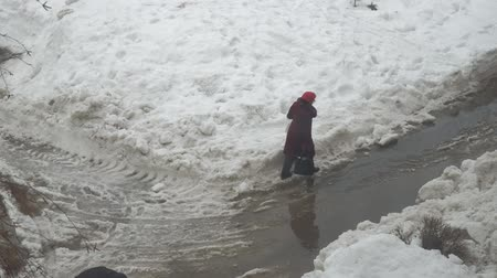 runoff water : Woman go through a puddle and sleet, wet snow