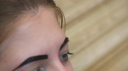 tweezing : Beautician performs eyebrow correction for a young woman. Eyebrow care