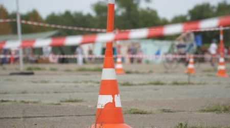 dividing : Fencing tape and road cone on the background of passing people. Selective focus