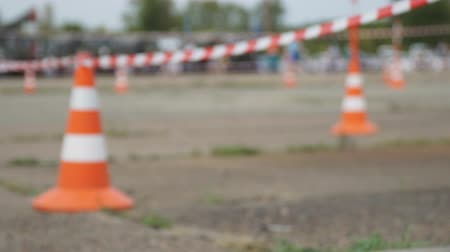 enclosure : Blurred view. Fencing tape and road cone on the background of passing people Stock Footage