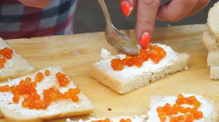 консервированный : Woman makes sandwiches with red caviar and wheat bread Стоковые видеозаписи