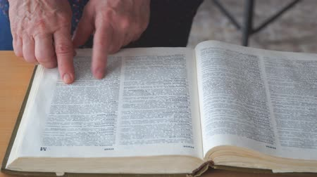 bible study : Hand over a large book. Finger over the letters. Search for information in the dictionary