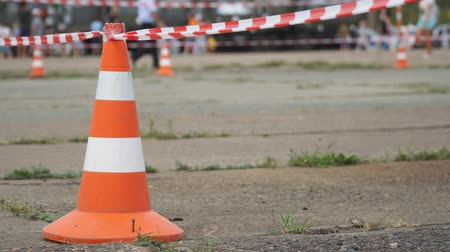 moloz : Fencing tape and road cone on the background of passing people. Selective focus