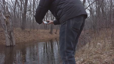 A man takes a picture on his phone of running water in a small forest river on a cloudy autumn day. Late autumn Stock Footage