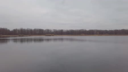 Panorama of a large lake or river on a cloudy dark autumn day