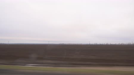 View of a plowed field from the window of a car driving on the road