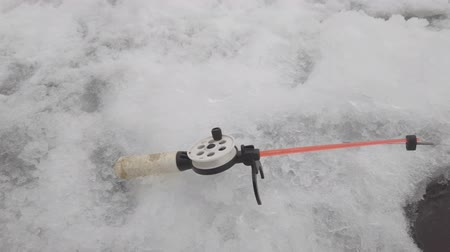 Fishing rod for winter fishing near the ice hole. Winter fishing Stock Footage