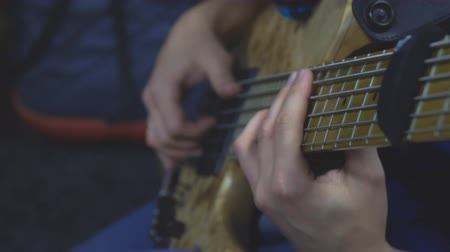 The bass player plays on a five-string bass guitar close-up. Plays bass guitar. Selective focus Stock Footage