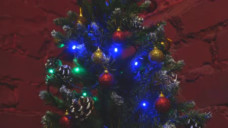 A small Christmas tree decorated with Christmas toys on the background of a red brick wall