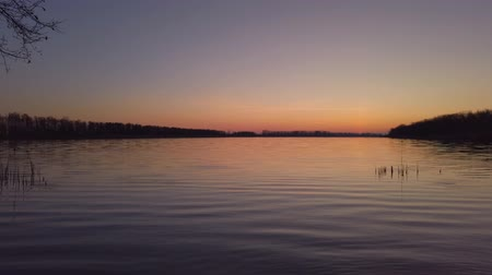 Summer sunset on a quiet lake. Camera panning