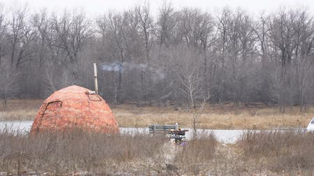 Tourist tent with a pipe on the lake in late autumn. The tent is heated, smoke comes out of the chimney and the wind blows it