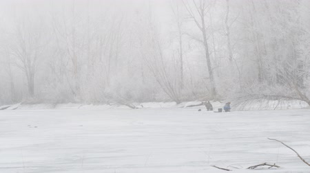Winter river in the fog. Fishermen on the ice fishing. The trees are beautiful hoarfrost Stockvideo