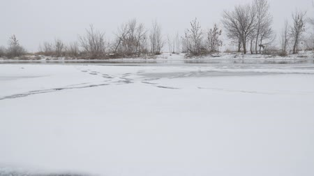 frozen lake : Frozen winter river with open water on a cloudy foggy day