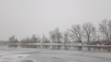 Frozen winter river with open water on a cloudy foggy day