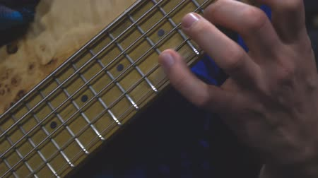 The bass player plays on a five-string bass guitar close-up. Plays bass guitar. Selective focus Стоковые видеозаписи