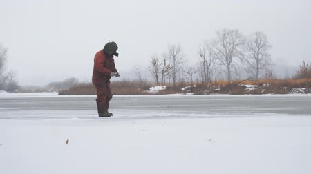 A fisherman on the ice of a frozen river catches fish. Winter Ice fishing