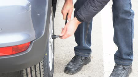 replace : A man tightens the nuts on the wheels of the car. Checking the tightening of wheel nuts