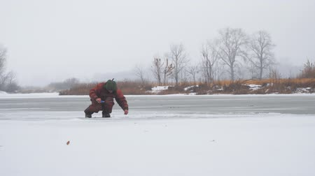 зажимное приспособление : A fisherman sits on the ice of a frozen river and catches fish. Winter Ice fishing