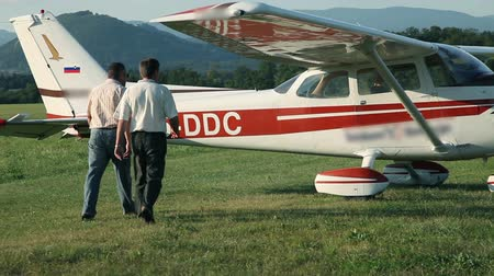 vista frontal : Medium shot of two man going in to small airplane Stock Footage