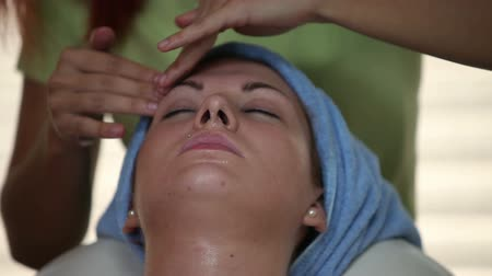 masaż twarzy : Close up of massaging womans face with oiled hands Wideo